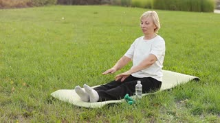 Mature woman doing sports on the street. Flexibility of ligaments and joints in old age
