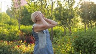 Mature woman enjoying nature and sun in the garden