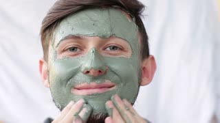 Men's cosmetology at home. A young cute guy using a clay mask on his face
