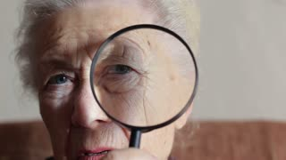 old lady looking through a magnifying glass