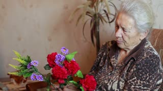 Old woman holding a bouquet of artificial flowers. Close up