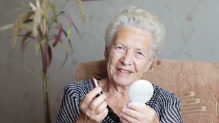 Old woman holding makeup in hands. The concept of Beauty and elegance in old age