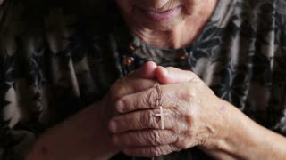 Old woman praying to God. Daily traditional Catholic devotional of an old lady or woman