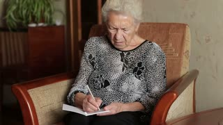 Old woman tries to remember what to write on paper. Grandmother with a bad memory