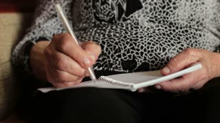 Old woman writing something in notebook