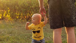 Paternity. Happy kid learns to walk with the help of his father