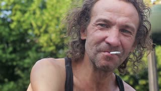 Portrait of a drunken homeless man. He smokes and looks at the camera