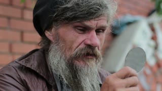 portrait of a homeless man looking at himself in the mirror