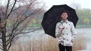 Portrait of a nice young man under an umbrella. He smiles and looks at the camera