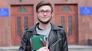 Portrait of a young student against the background of the university. He is happy at the start of the school year and showing his thumbs up
