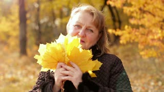 Portrait of an elderly woman in an autumn park. She is holding a bouquet of yellowed leaves in her hands and looking at the camera