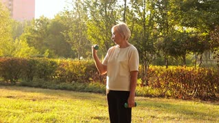 Positive elderly woman exercising with dumbbells outdoors