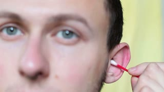Procedure for cleaning the ears with cotton swabs close up
