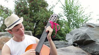 romantic musician relaxing in nature with a guitar. The young man sitting under a tree hugging his guitar and composing the motif of a new melody