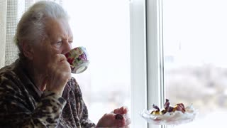 Sad old woman looking out the window and drinking tea. Close up