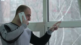 Sad young man talking on cellphone by the window.