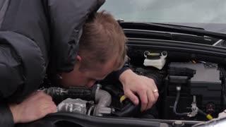 Sad young man with broken car