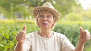 Satisfied elderly woman smiling and showing thumb up