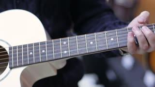 Shop musical instruments. Close up of a Young Man chooses a guitar