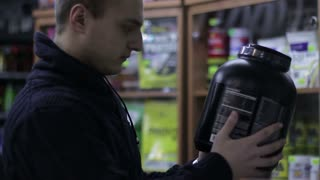 Shop of sports nutrition. Young Man chooses protein