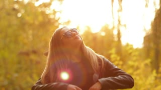 Silhouette of a girl in sunglasses at sunset. She lifting her hands up to the sun and enjoying the warmth