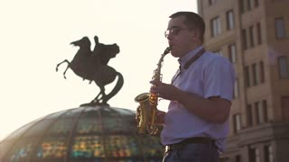 Silhouette of a musician playing the saxophone on the street