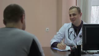 Smilling young doctor talking with patient in his office.