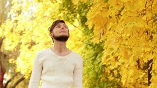 stylish bearded guy enjoying the warm autumn weather in the park