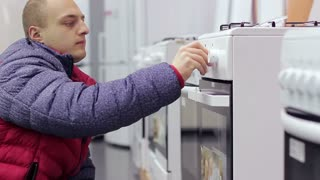 the buyer chooses a stove in the kitchen at a home appliance store