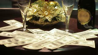 The composition: on the table a bottle of champagne, two glasses, and dollars. Also, dollar lie on the floor