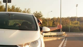 The driver leaning out of the window showing his thumb up in motion