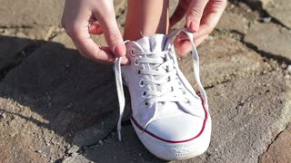 The girl Tying her shoelaces on white sneakers. Close-up