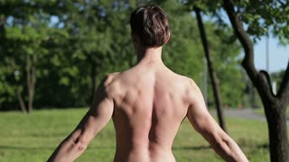 The guy is posing in nature. Back view