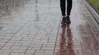 The guy's feet are walking along the wet pavement Close-up