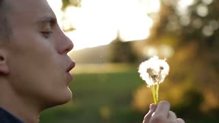 The man ineptly blowing down the fluff from the dandelion