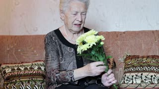 The old woman holding a bouquet of flowers in her hands