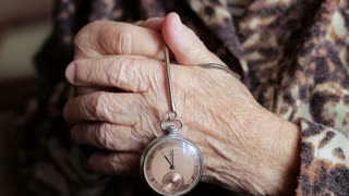 The old woman is holding an old pocket watch.