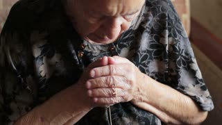 The old woman prays to the god. Grandmother holds a cross in her hands and reads a prayer