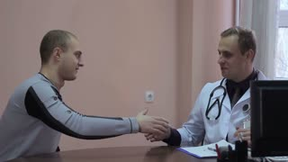 The patient thanks the doctor. He shook hands with the doctor. Close-up