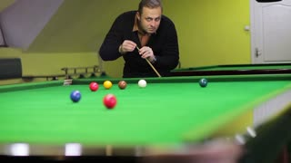 The player evaluating the position on the snooker table and striking the ball