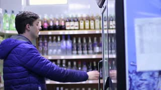 The young buyer buying a drink in the supermarket