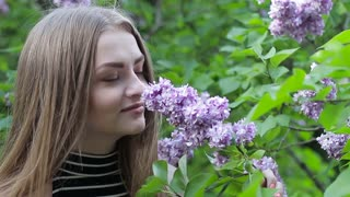 The young girl smells lilac flowers
