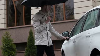 The young guy gets into the car in the rain. He folds the umbrella and goes inside
