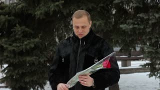 The young guy in a fur jacket is waiting for his girlfriend and smelling a rose
