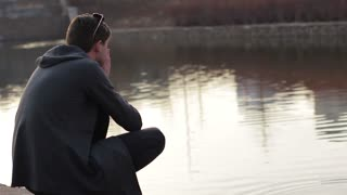 The young guy meditating on the shore of the pond