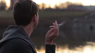 The young guy smoking near the river. Close-up