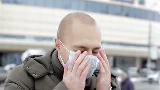 The young man in the mask is sick with the flu, he sneezes and coughs