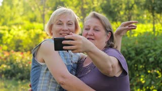 Two mature women taking pictures and having fun together in the park