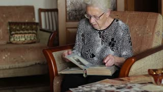 Very Old Woman Looking At A Photo In Old Photo Album, Memories