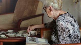 Very old woman looking at old photos